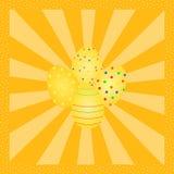 在橙色射线样式的四个五颜六色的复活节彩蛋 免版税库存照片