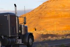 在橙色山背景的半黑暗卡车 免版税库存照片