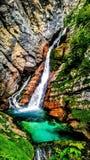 在橙色岩石的美丽的瀑布 库存图片