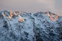 在橙色日落天空,朱利安阿尔卑斯,斯洛文尼亚的田园诗高山多雪的山脉峰顶视图 免版税库存图片