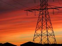 在橙色日落的输电线 库存图片
