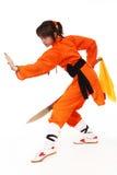 在橙色服装的女孩wushu在低卫兵 免版税图库摄影