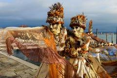在橙色服装的被掩没的夫妇 免版税库存照片