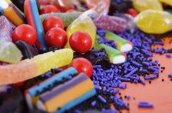 在橙色木背景的明亮的五颜六色的糖果 免版税库存照片
