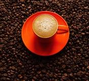 在橙色杯子的咖啡在茶碟用咖啡豆 免版税图库摄影