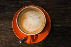 在橙色杯子的咖啡拿铁有木头的 图库摄影