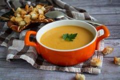在橙色板材的南瓜红萝卜奶油色汤用在一张被检查的桌布的薄脆饼干有木背景 库存图片