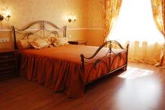 在橙色柔和的淡色彩设计的晴朗的浪漫卧室 免版税库存图片