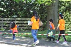 在橙色毛线衣的亚洲家庭,荷兰 库存照片