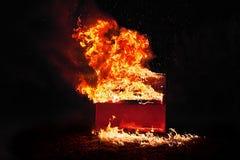 在橙色火焰的红色钢琴 图库摄影