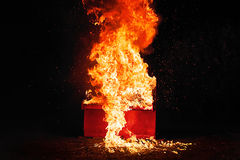 在橙色火焰的红色钢琴 库存照片