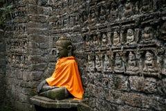 在橙色盖子的古老菩萨雕象 免版税库存照片