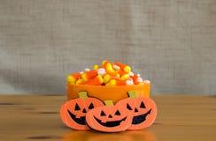 在橙色碗的糖味玉米有在一张木桌上的3个起重器o灯笼的 免版税库存照片