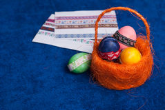 在橙色篮子的复活节彩蛋在蓝色背景, 免版税库存图片