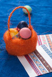 在橙色篮子的复活节彩蛋在蓝色背景, 库存图片