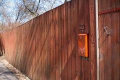 在橙色篱芭的橙色邮箱 库存照片