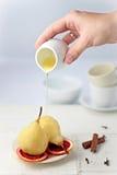 在橙色糖浆的水煮的梨 免版税库存图片