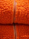 在橙色羊毛纹理背景的拉链 图库摄影