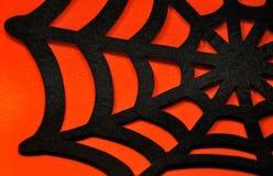 在橙色背景上的黑蜘蛛网 免版税库存照片