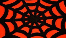 在橙色背景上的黑蜘蛛网 库存照片