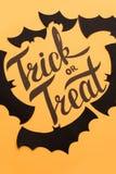在橙色背景和黑棒绘的商标万圣夜 免版税库存图片