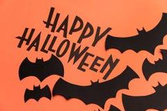 在橙色背景和黑棒绘的黑商标万圣夜 免版税库存照片