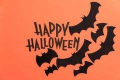 在橙色背景和黑棒绘的黑商标万圣夜 免版税库存图片