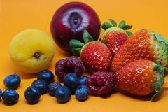 在橙色背景的各种各样的果子 图库摄影