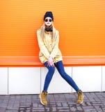 在橙色背景的城市塑造相当白肤金发的女孩 免版税库存照片