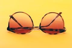 在橙色背景的夏天太阳镜 免版税库存照片