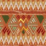 在橙色背景的手拉的部族种族五颜六色的无缝的样式 库存照片