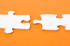 在橙色背景的白色难题零件 免版税库存照片