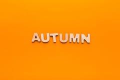 在橙色背景的词秋天 库存照片