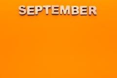 在橙色背景的词9月 库存照片