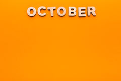 在橙色背景的词10月 库存图片