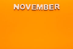 在橙色背景的词11月 免版税图库摄影