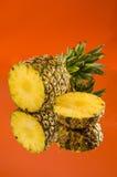 在橙色背景,垂直的射击的切的,说谎的菠萝 免版税图库摄影
