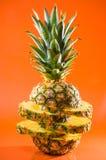 在橙色背景,垂直的射击的艺术性的切的,站立的菠萝 免版税库存照片