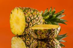 在橙色背景,水平的射击的切的,说谎的菠萝 免版税库存照片