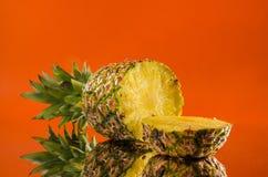 在橙色背景,水平的射击的切的,说谎的菠萝 库存图片