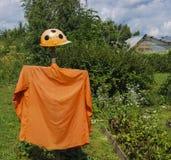 在橙色衬衣的一个明亮的稻草人 免版税库存图片