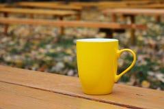 在橙色长凳的黄色杯 免版税库存照片