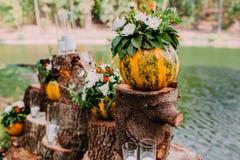 在橙色颜色的美好的婚礼装饰秋天婚礼 在湖附近的室外仪式 南瓜、花和蜡烛 库存照片