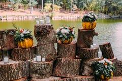 在橙色颜色的美好的婚礼装饰秋天婚礼 在湖附近的室外仪式 南瓜,花,和 库存照片