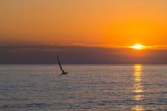 在橙黄和紫色日落的小风船航行 库存照片