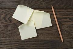 在橡木桌上的稠粘的笔记提示与铅笔 库存照片