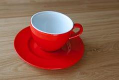 在橡木桌上的红色空的杯子 免版税库存图片