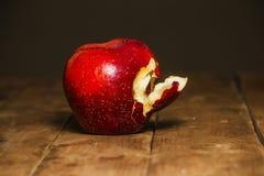 在橡木桌上的红色被咬住的苹果 在桌关闭咬住的苹果计算机红色  免版税库存图片