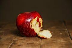 在橡木桌上的红色被咬住的苹果 在桌关闭咬住的苹果计算机红色  库存照片