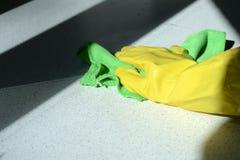 在橡胶太阳点燃的手套洗涤的表面的手 库存图片